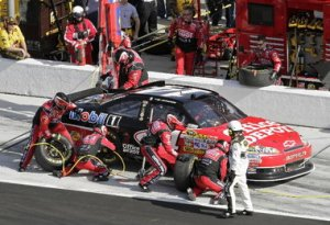 NASCAR crew members in action during pit stop.