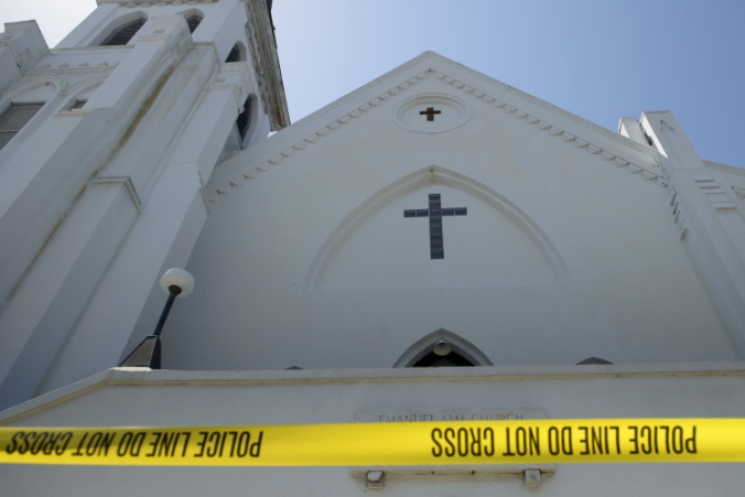 Police tape is seen outside the Emanuel AME Church, after a mass shooting at the Emanuel AME Church the night before  in Charleston, South Carolina on June 18, 2015. Police captured a white suspect in a mass killing at one of the oldest black churches in the United States, the latest gun massacre to leave the country reeling. Police detained 21-year-old Dylann Roof, shown wearing the flags of defunct white supremacist regimes in pictures taken from social media, after nine churchgoers were shot dead. AFP PHOTO/BRENDAN SMIALOWSKI        (Photo credit should read BRENDAN SMIALOWSKI/AFP/Getty Images)